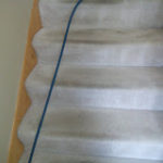 Heavily soiled light colored carpeted steps.